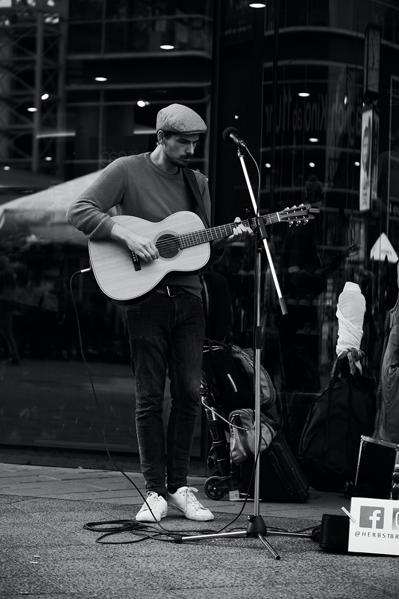 solo acoustic guitarist playing outside with microphone on stand